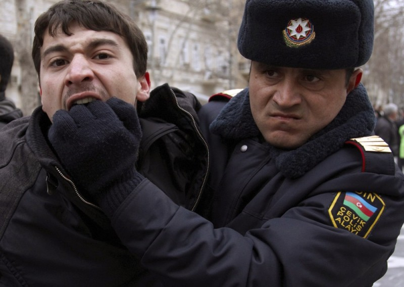 A policeman detains an opposition activist in Baku March 12, 2011 - REUTERS/Orhan Orhanov