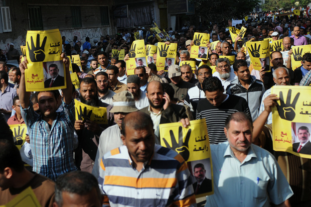 Supporters of Egypt's ousted President Mohammed Morsi in Helwan District raise his poster and their hands with four raised fingers, which has become a symbol of the Rabaah al-Adawiya mosque. (Nameer Galal / Demotix)