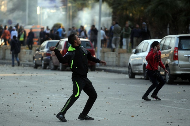 An alleged supporter of ousted President Mohamed Morsi clashes with Egyptian security forces in front of Cairo University, Egypt 12th January 2014 (Image: Nameer Galal/Demotix)