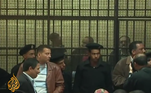 Defendants in Egypt's NGO trial held in cages during proceedings (Image: Al Jazeera English/YouTube)