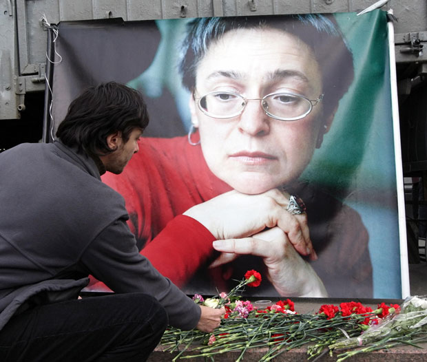 A man lays flowers near the picture of murdered journalist Anna Politkovskaya, during a rally in Moscow, Russia, 7 October 2009. CREDIT: EPA / Alamy Stock Photo