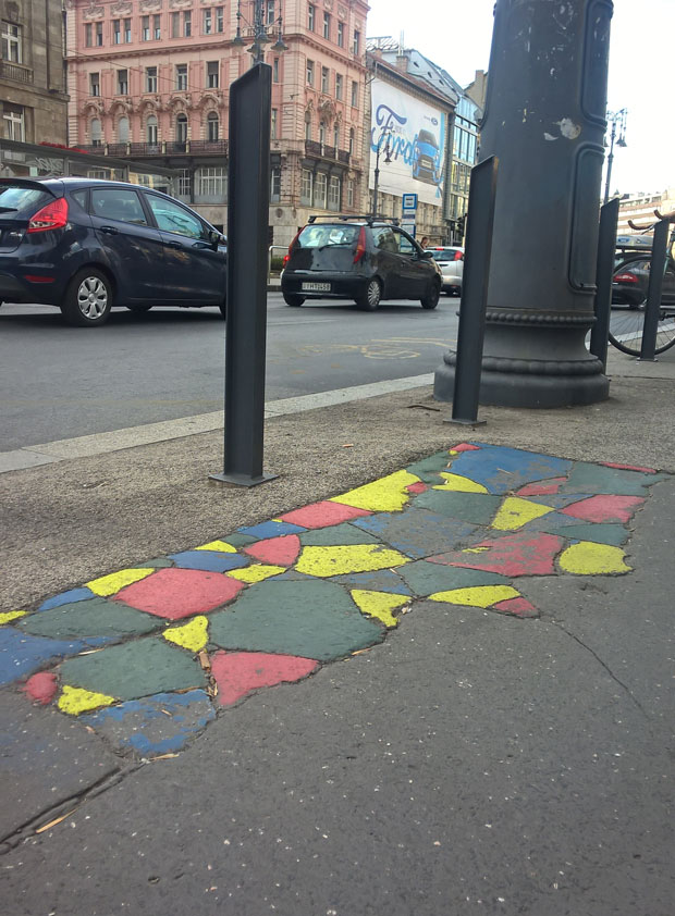 Anonymous volunteers have joined the satirial political party the Two-Tailed Dog party (MKKP) to paint cracked pavement on the streets of Budapest. Image: Fruzsina Katona