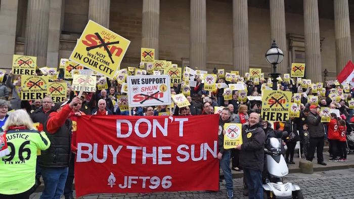 Protesters hold placards asking people not to buy the Sun