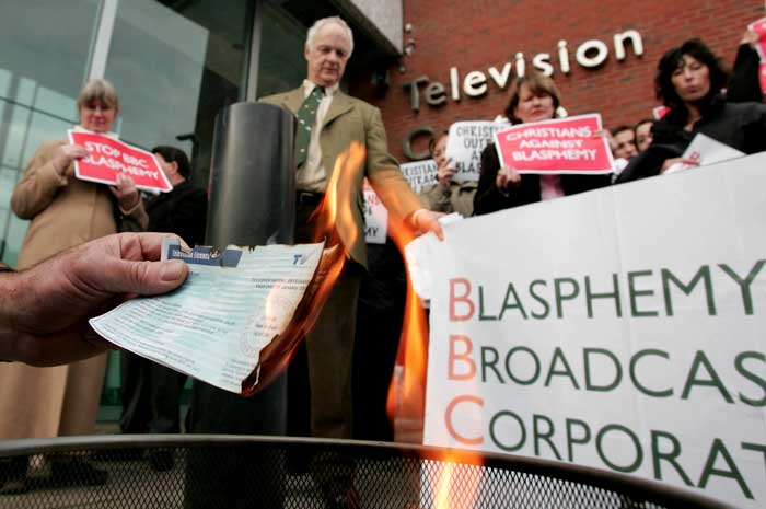 Members of Christian organisations burn TV licenses during a demonstration outside the BBC,