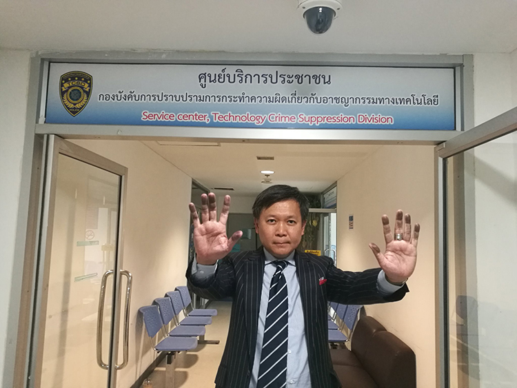 Pravit Rojanaphruk shows his ink-stained hands after being fingerprinted at the Royal Thai Police's Technology Crime Suppression Division in Bangkok, August 8, 2017.