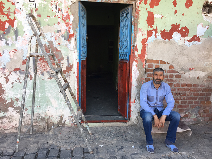 "Cumali, sitting in front of his evacuated house, did not want to leave Sur. He has been moved to temporary housing on a road that has not yet been demolished. Cumali says, ""I was born in Sur, I grew up, got married, let us relax, I want to die in Sur."""