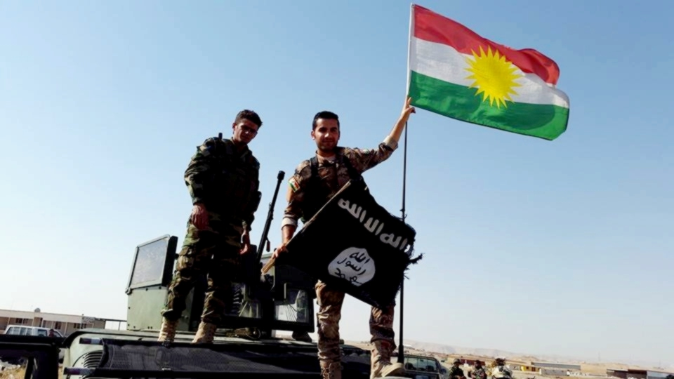 Iraqi Kurdistan military forces, the Peshmerga, replace an ISIS flag with the Kurdish flag near Mosul, Iraq, Kurdishstruggle/Flickr