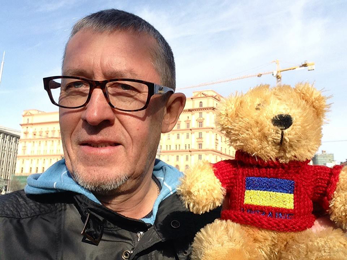 Russian journalist Alexander Shchetinin, pictured in front of the former headquarters of the KGB in Moscow with a stuffed bear.