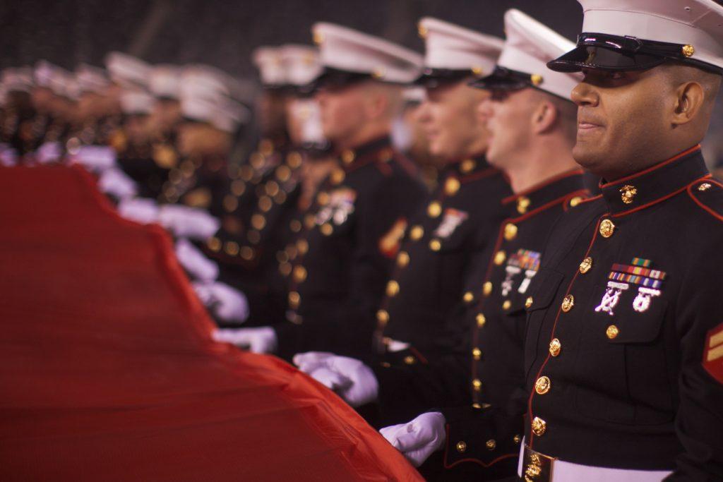 Soldados, pilotos de las fuerzas aéreas y marines desenrollan una bandera estadounidense en una ceremonia de apreciación del ejército en un partido de los New York Jets contra los New England Patriots el 13 de noviembre de 2011, Sargento Sandall A. Clinton/Flickr