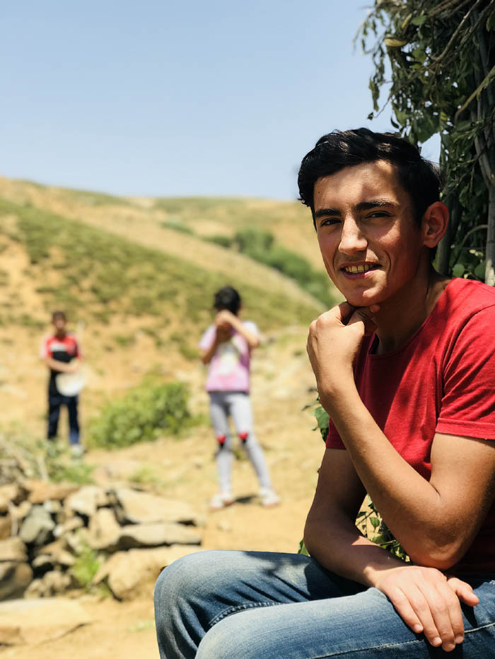 İdris Sayılgan's 18-year-old İsmail who guided us to the meadow, with Hivda and Yunus in the background. (Credit: Mezopotamya Agency)
